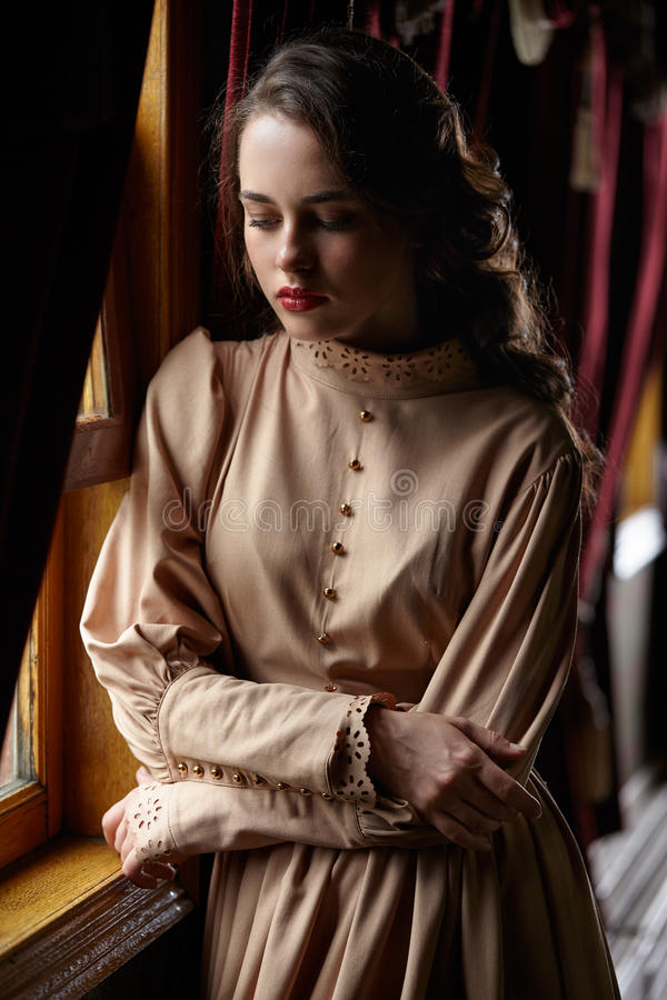 Young woman in beige vintage dress of early 20th century standin. G near window in corridor of retro railway train stock photos
