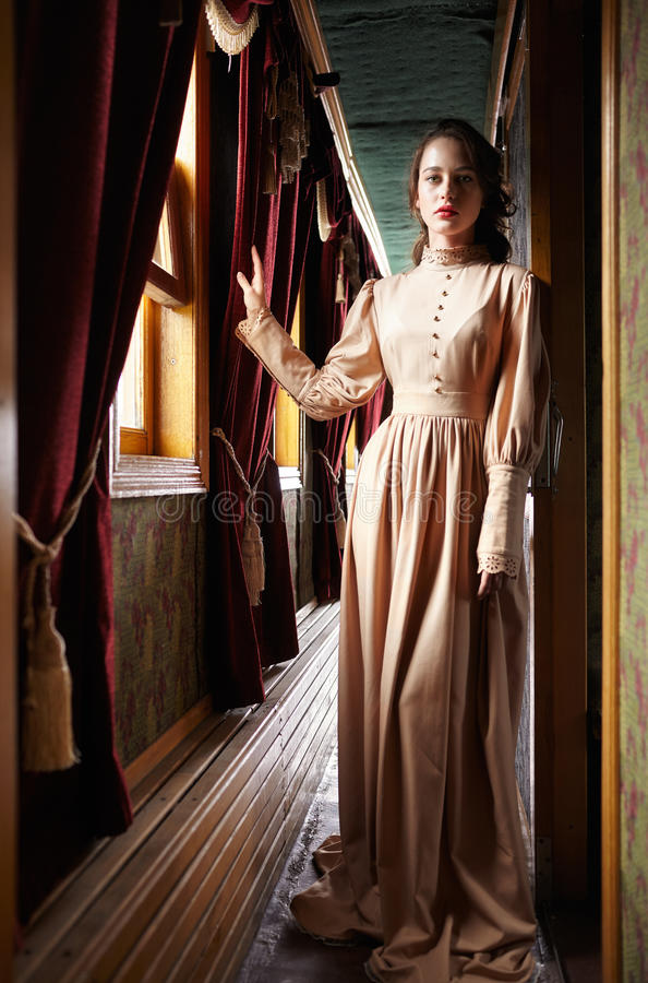 Young woman in beige vintage dress of early 20th century standing near window in corridor of retro railway train stock photos