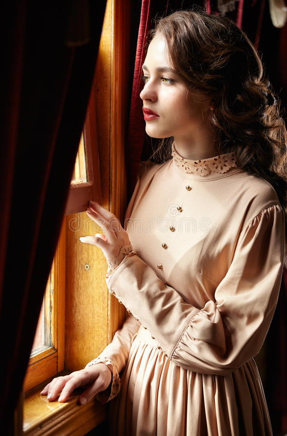 Young woman in beige vintage dress of early 20th century standing near window in corridor of retro railway train royalty free stock photography