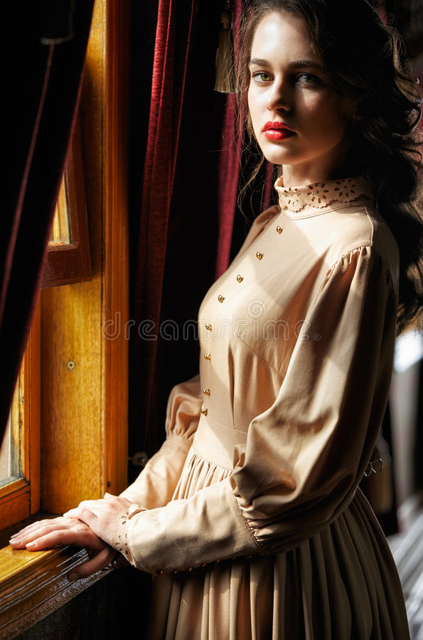 Young woman in beige vintage dress of early 20th century standin. G near window in corridor of retro railway train royalty free stock images
