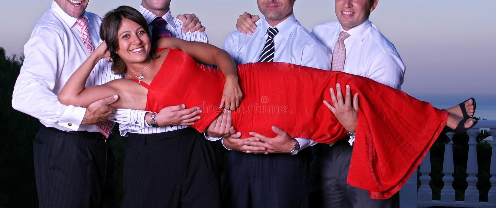 Young woman being lifted by four men at a party stock image