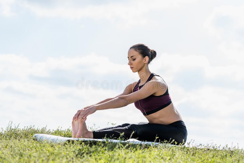 young woman bending forward while practicing stock images