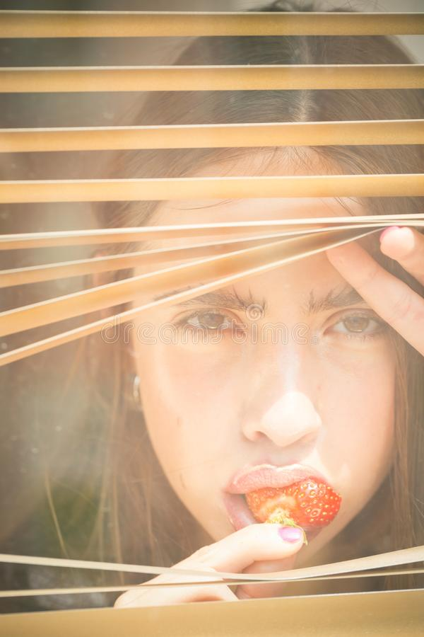 Young woman with berry in mouth. Girl eat red strawberry and look in window. Summer, ripe fruit, harvest season. Food, healthy diet, dieting. Nutrition royalty free stock photo