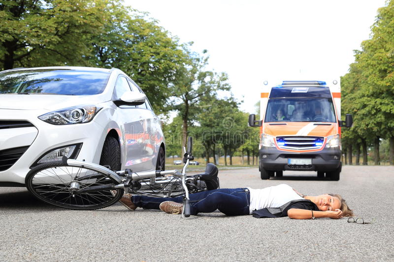 Young Woman with bicycle accident and comming ambulance car royalty free stock photos