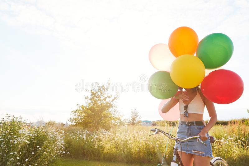 Young Woman With Bicycle Hidden By Balloons Rides Through Countryside Against Flaring Sun royalty free stock photo