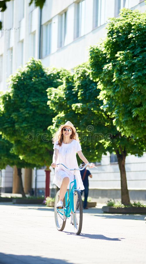 Young woman on bicycle rides alone down the city street stock image