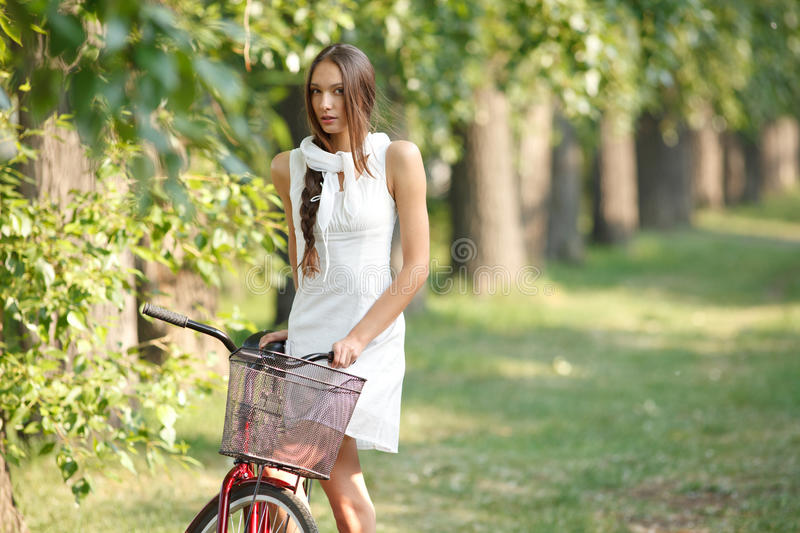 Young woman with bicycle. Young sensual woman in white with bicycle outdoors. Professional style royalty free stock image