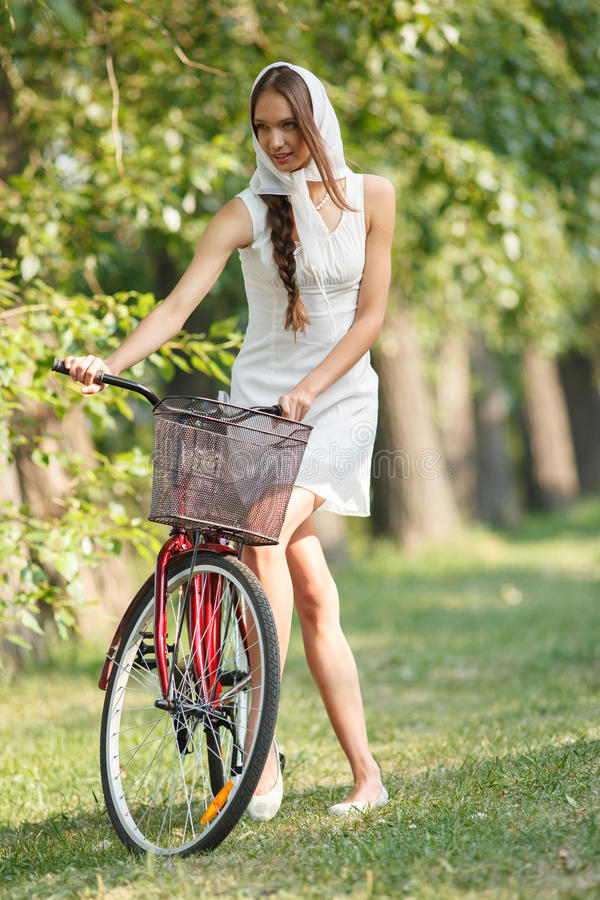 Young woman with bicycle. Young sensual woman in white with bicycle outdoors. Professional style royalty free stock images
