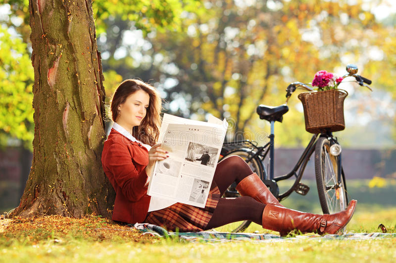 Young woman with bicycle sitting on a grass and reading a newspaper. Young woman with bicycle sitting on a green grass and reading a newspaper in a park stock photography