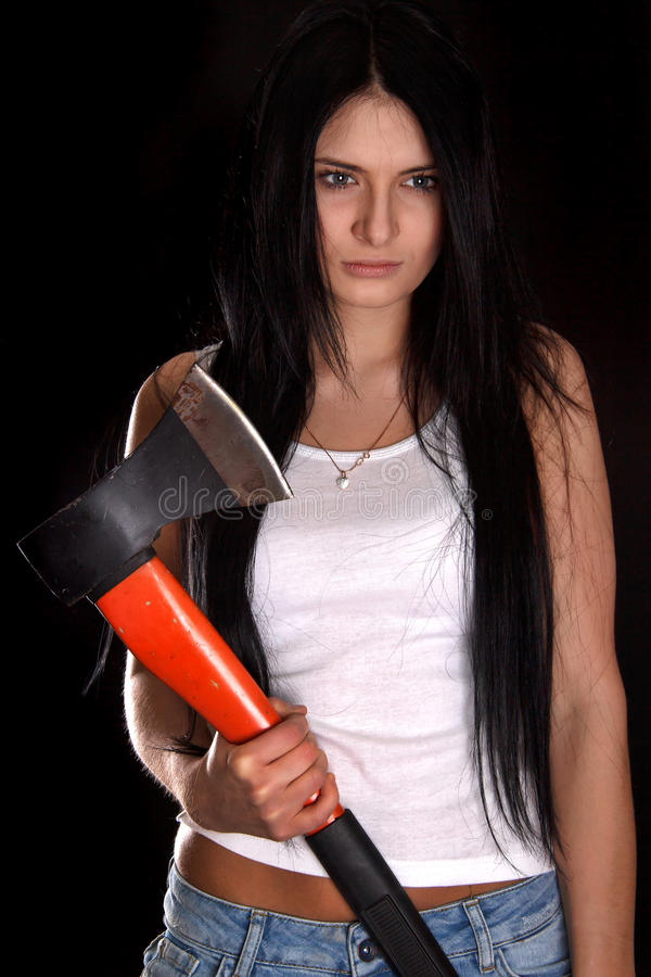 Young woman with a big axe. Over black background royalty free stock images