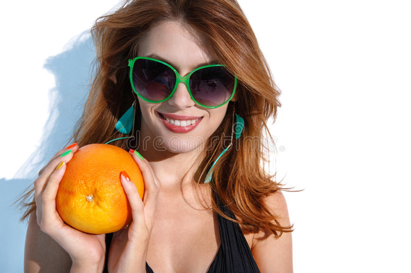 Young woman with big orange. Portrait of amazing girl wearing swimsuit holding an orange in her hands on white background royalty free stock photography