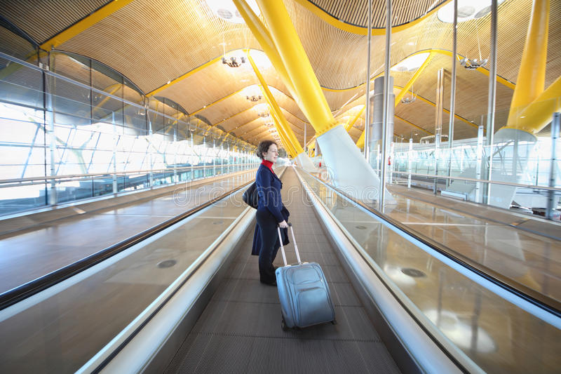 Young woman with big travel bag stands in hallway stock photography