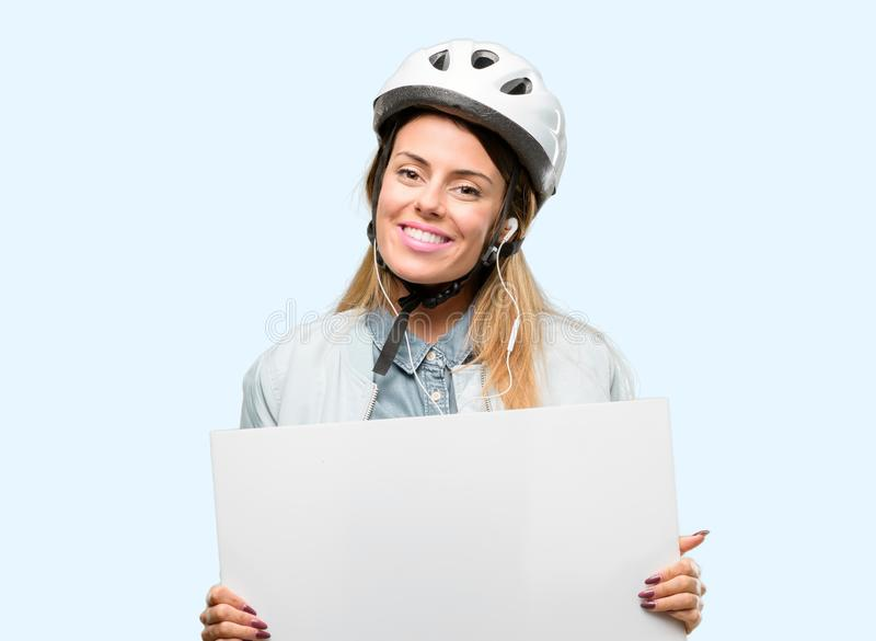 Young woman with bike helmet and earphones over blue background royalty free stock images