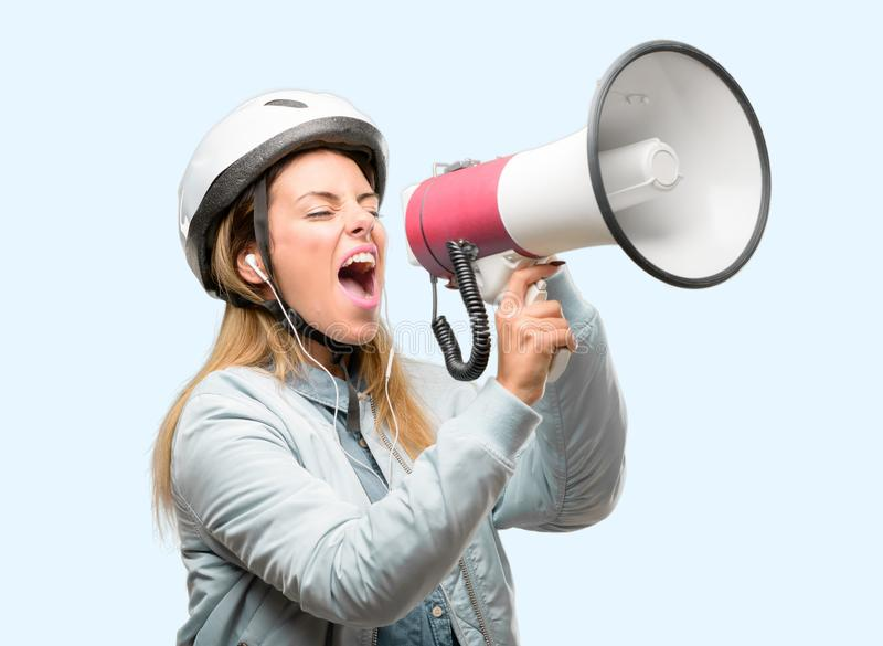 Young woman with bike helmet and earphones isolated over blue background. Young woman with bike helmet and earphones communicates shouting loud holding a royalty free stock photo
