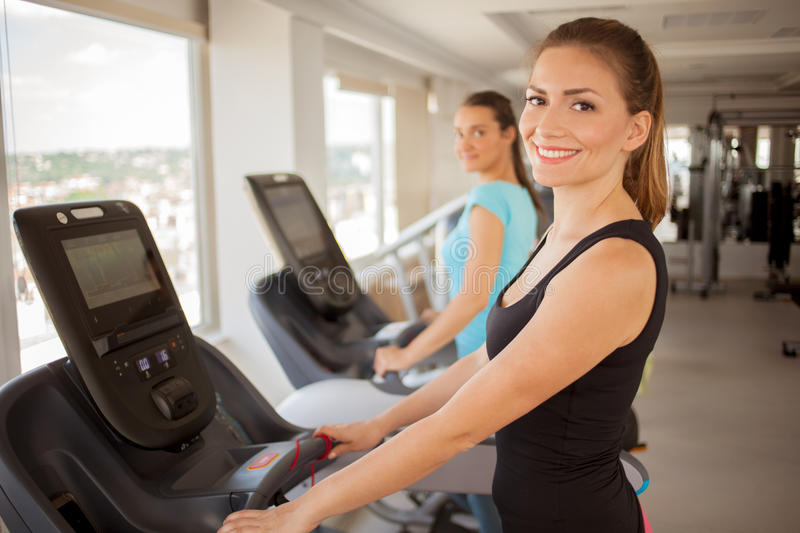 Young woman biking in the gym, exercising legs doing cardio wor royalty free stock image