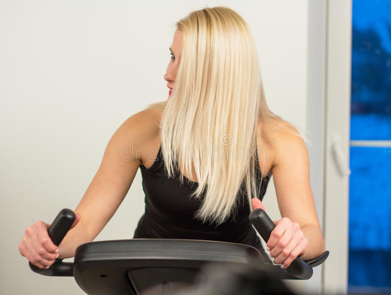Young woman biking in the gym, exercising legs doing cardio workout cycling bikes royalty free stock images