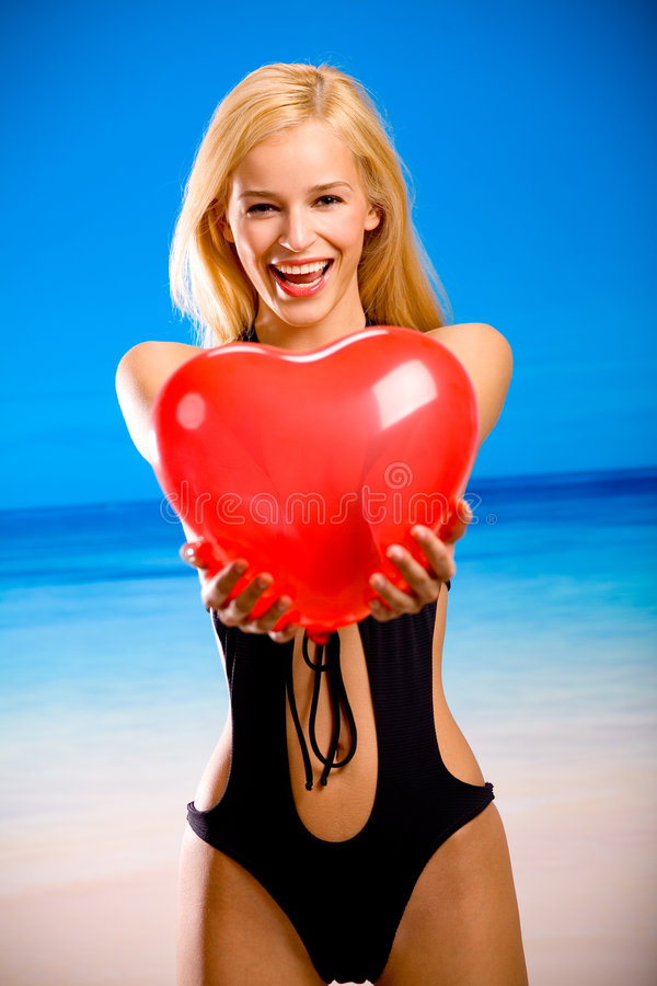 Young woman in bikini. Young beautiful smiling tanned blond woman in bikini on tropical sea beach, holding valentine balloon royalty free stock photography