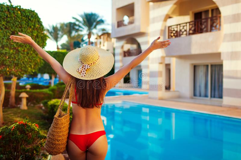 Woman relaxing by swimming pool. Summer vacation. All inclusive. Happy girl raising arms. Young woman in bikini and hat relaxing by swimming pool. Summer royalty free stock images