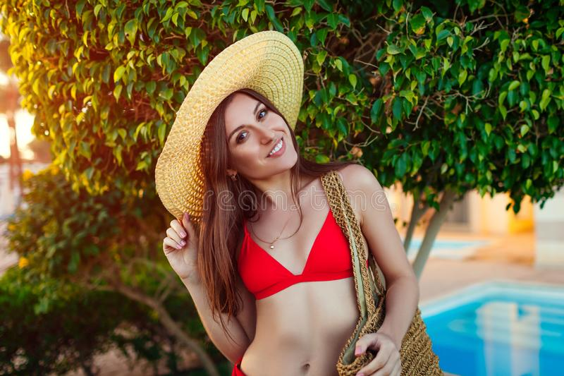 Woman relaxing by hotel swimming pool. Summer vacation. All inclusive. Happy girl walking in garden. Young woman in bikini and hat relaxing by swimming pool stock image