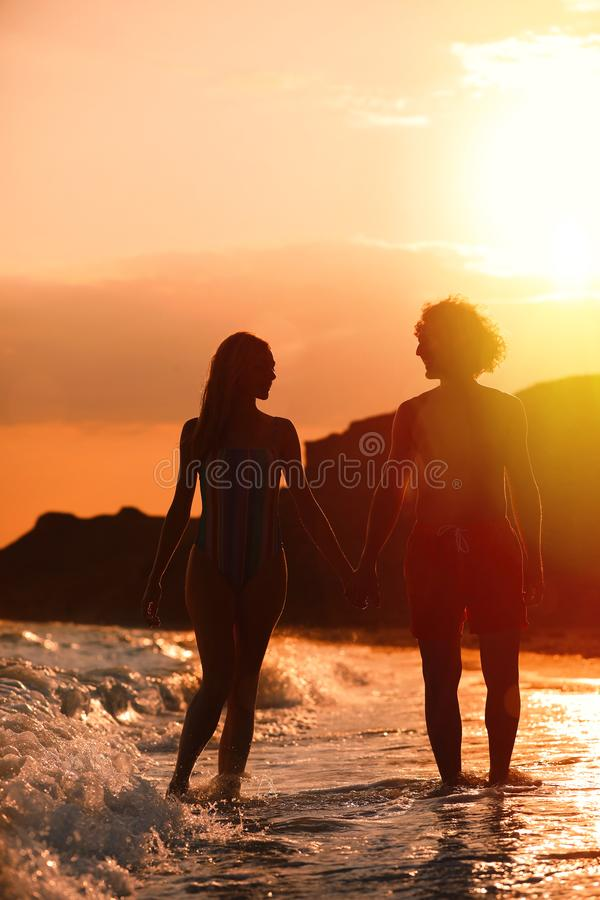 Young woman in bikini and her  on beach at sunset. Lovely couple. Young woman in bikini and her boyfriend on beach at sunset. Lovely couple stock image