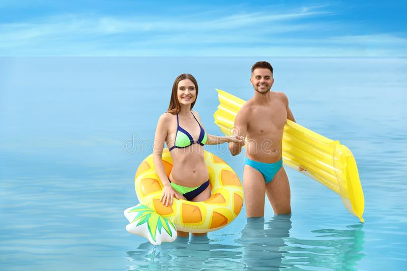 Young woman in bikini and her boyfriend with inflatable toys on beach. Young women in bikini and her boyfriend with inflatable toys on beach. Lovely couple stock images