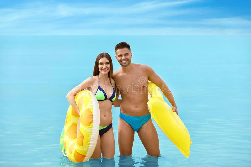 Young woman in bikini and her boyfriend with inflatable toys. Lovely couple. Young women in bikini and her boyfriend with inflatable toys on beach. Lovely couple royalty free stock images