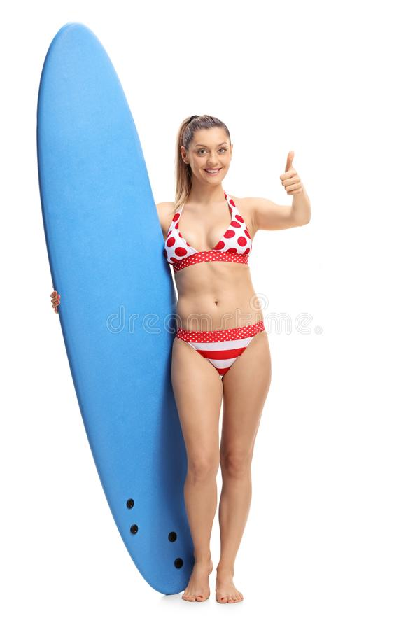 Young woman in bikini holding a surfboard and making a thumb up royalty free stock photos