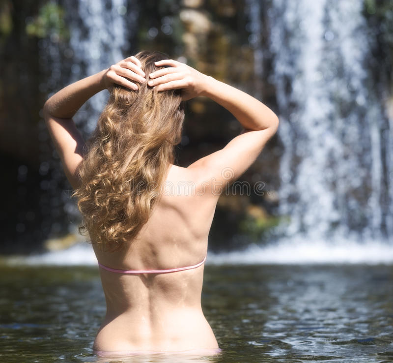 Young woman in a bikini standing in a natural pool royalty free stock image