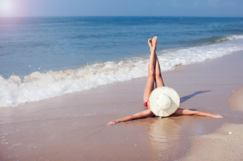 A young woman in bikini and in straw hat lying on a tropical beach, stretching up slender legs. Blue sea in the background. royalty free stock photo