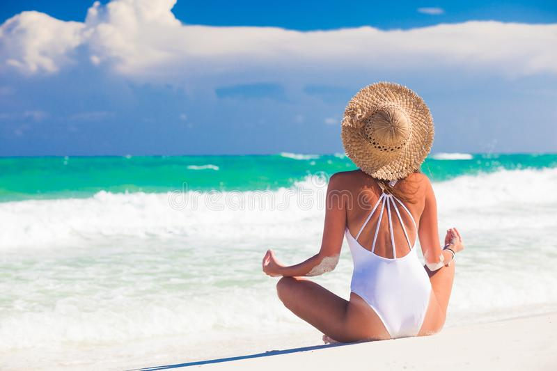 Young woman in bikini and straw hat relaxing at white caribbean beach stock images