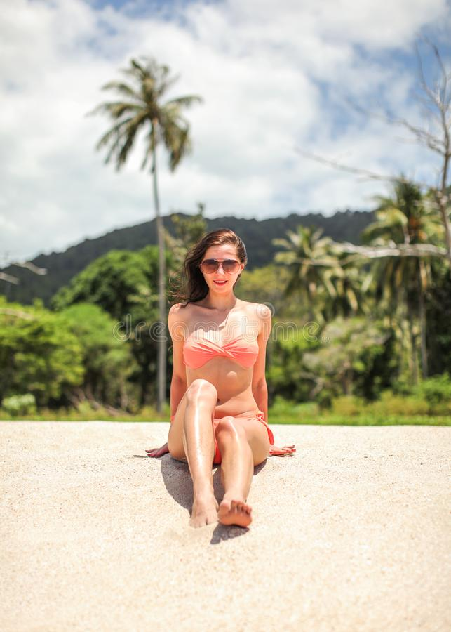 Young woman in bikini and sunglasses sitting on beach sand, looking into camera, palms and sky with clouds behind her royalty free stock images