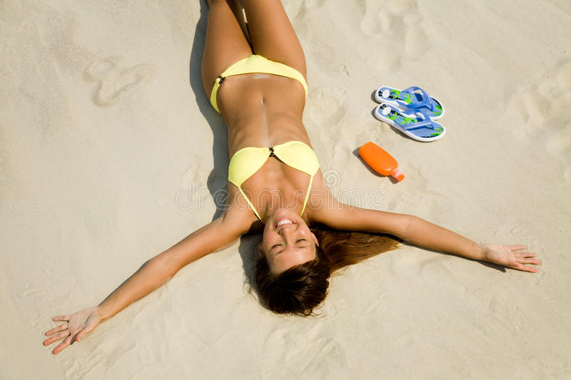 Young woman in bikini sunning on the beach. Beautiful young woman in bikini lying and sunning on the beach under the bright sun royalty free stock photography