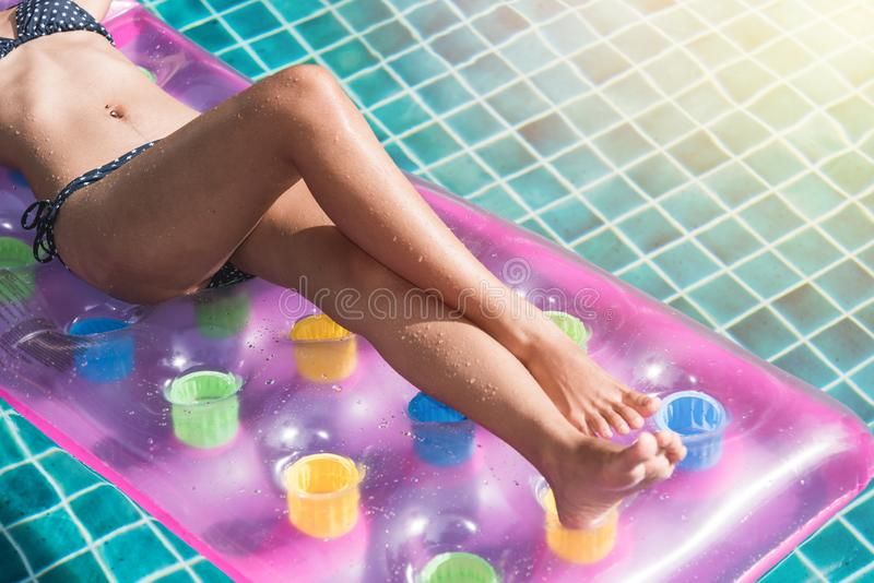 Young woman in bikini swimming pool on mattress inflatable floating royalty free stock photos