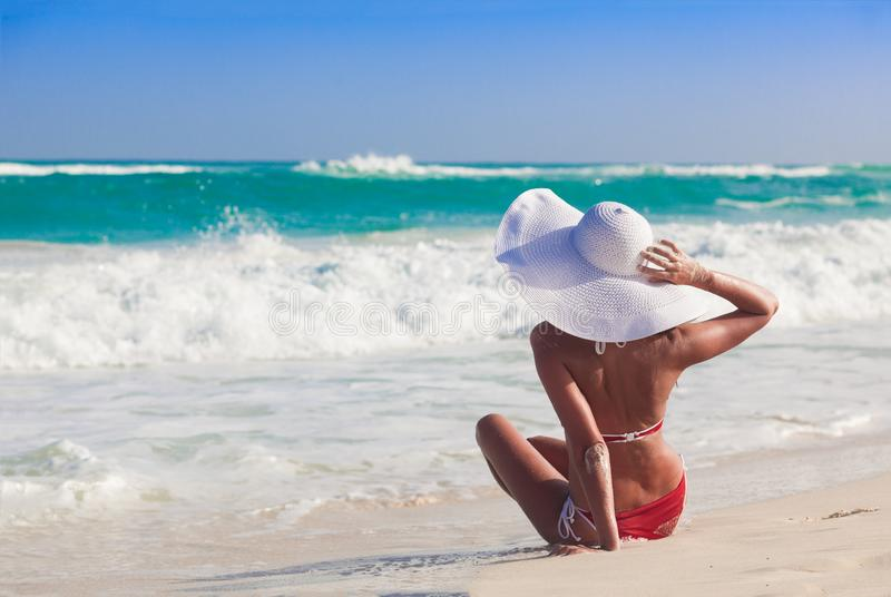 Young woman in bikini and white straw hat relaxing at white caribbean beach stock photography