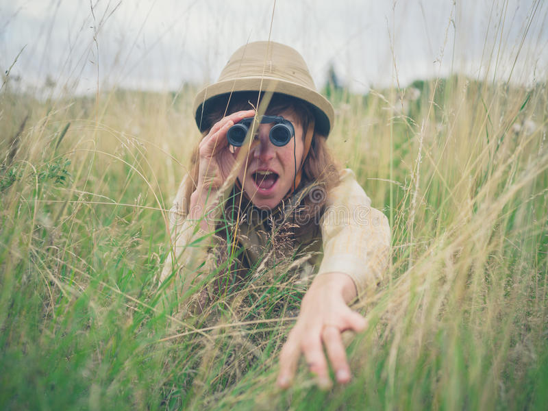 Young woman with binoculars in the grass royalty free stock images