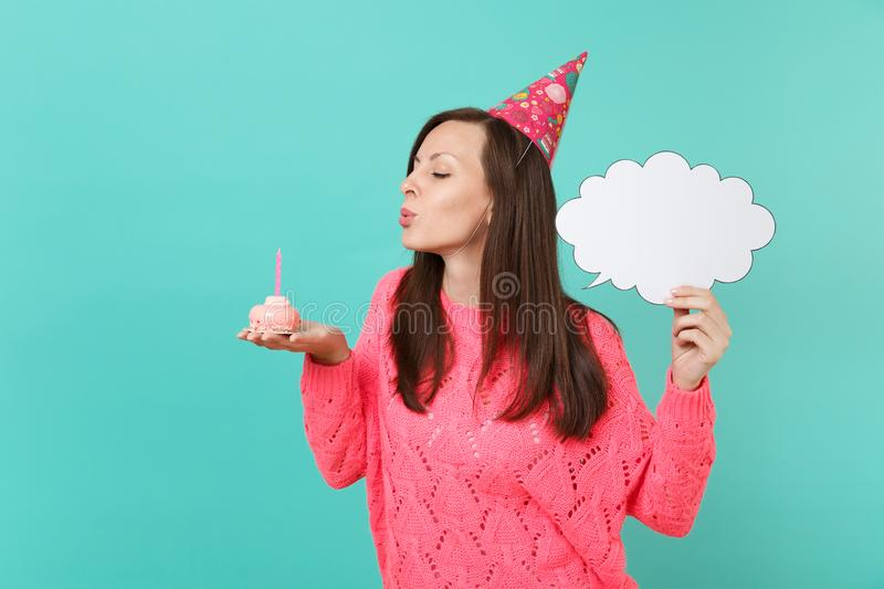 Young woman in birthday hat blowing out candle on cake, holding empty blank Say cloud, speech bubble for promotional. Content isolated on blue background royalty free stock photo