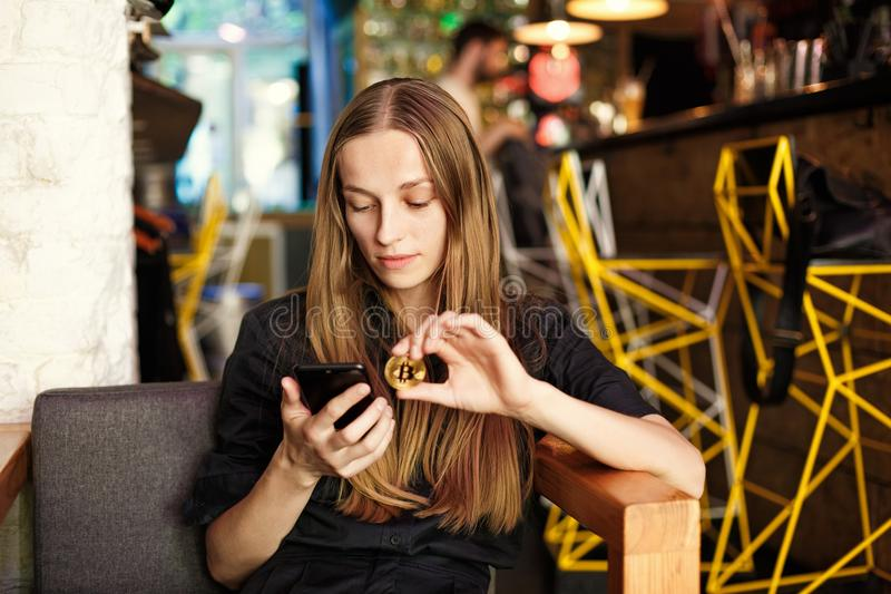 Young woman with a bitcoin and smartphone sits in a cafe royalty free stock photography
