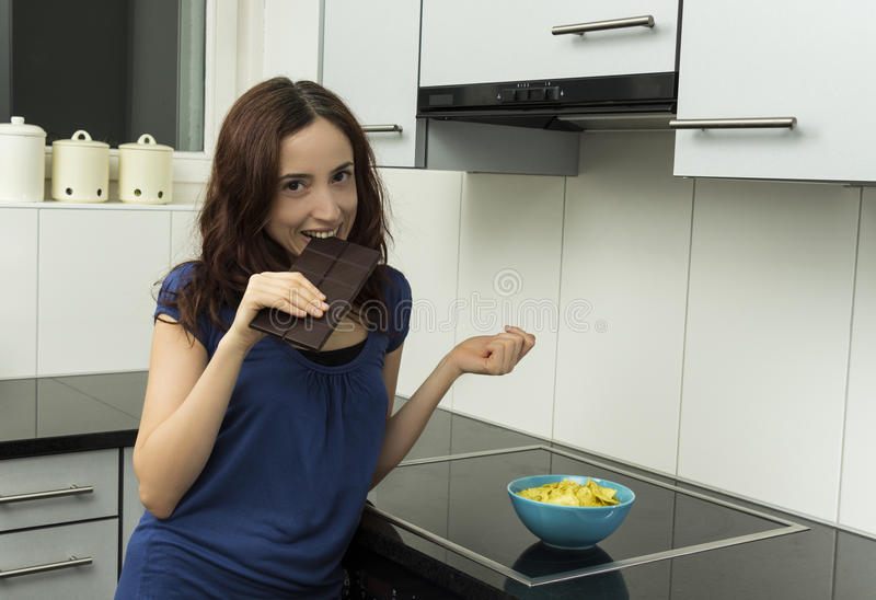 Young woman biting a block of dark chocolate. Young woman is biting a piece of dark chocolate with a smile royalty free stock photo