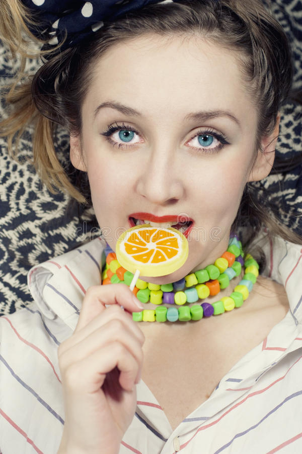 Young woman biting sugar candy. Portrait of young woman biting sugar candy royalty free stock photography