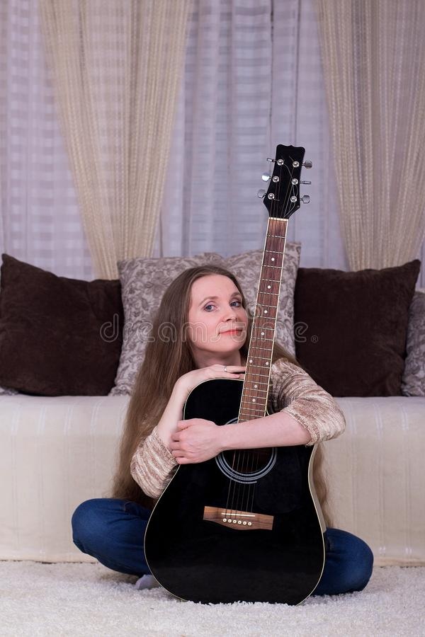 A young woman with a black acoustic guitar sitting on the carpet in the room stock photo