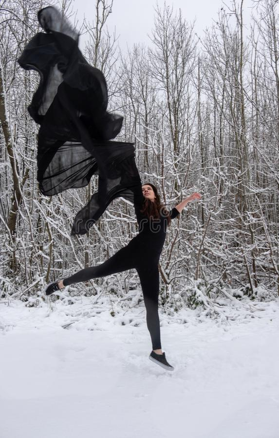 Young woman in black ballet suit jumping in the snowy forest with a black cloth in the air stock photos
