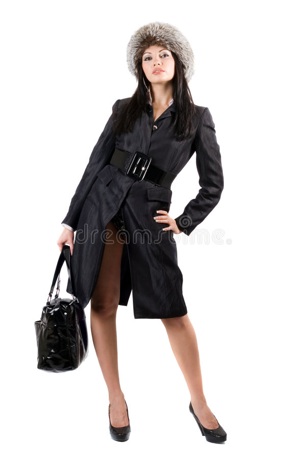 The young woman in a black coat and a fur cap. Isolated royalty free stock image