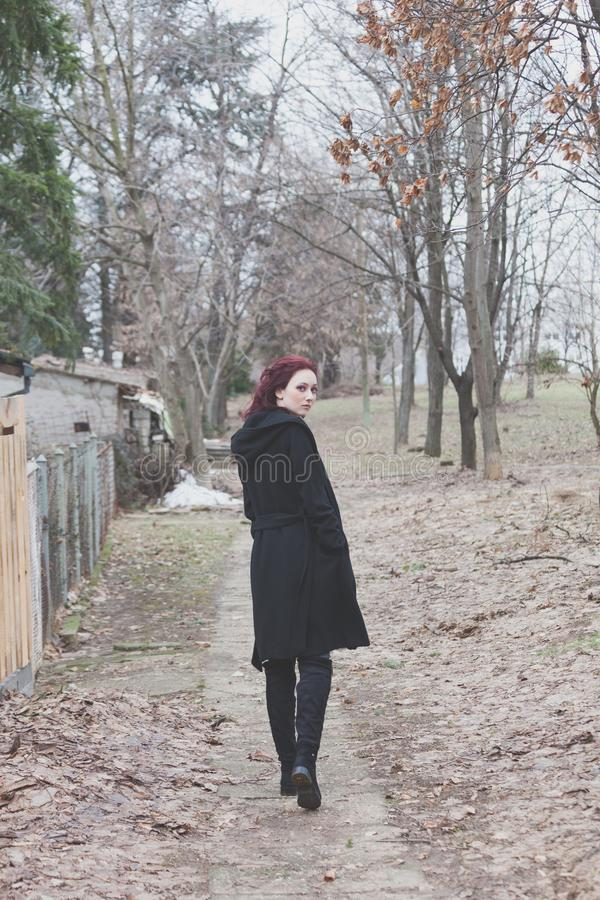 Young woman in black coat walk on path outdoor in park look back winter stock photos