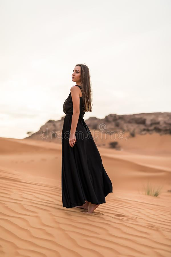 Young pretty woman in black dress dancing in sandy desert at sunset stock images