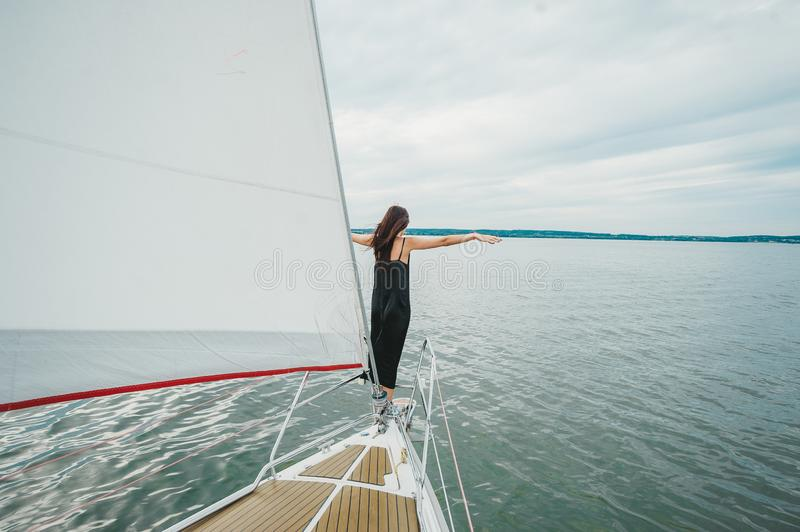 Young woman in black dress enjoying the beauty of the nature on sailing yacht sailing the sea stock photos