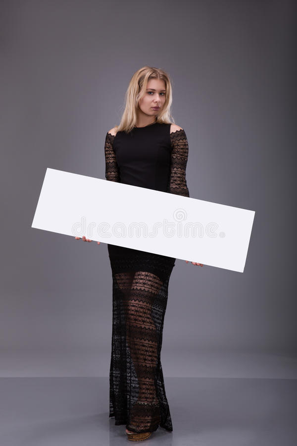 Young woman in black dress holding blank poster. stock photo