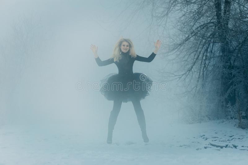 A young woman in a black dress jumps winter forest stock images