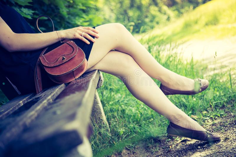 Summer in the park: Young woman in sexy black dress and ballerinas is sitting on a park bench. Young woman in black dress with sexy legs and leather handbag is royalty free stock image