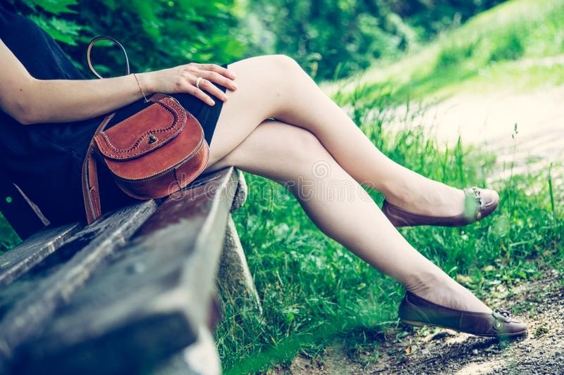 Summer in the park: Young woman in sexy black dress and ballerinas is sitting on a park bench. Young woman in black dress with sexy legs and leather handbag is stock image