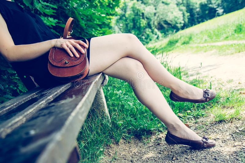 Summer in the park: Young woman in sexy black dress and ballerinas is sitting on a park bench. Young woman in black dress with sexy legs and leather handbag is royalty free stock photos